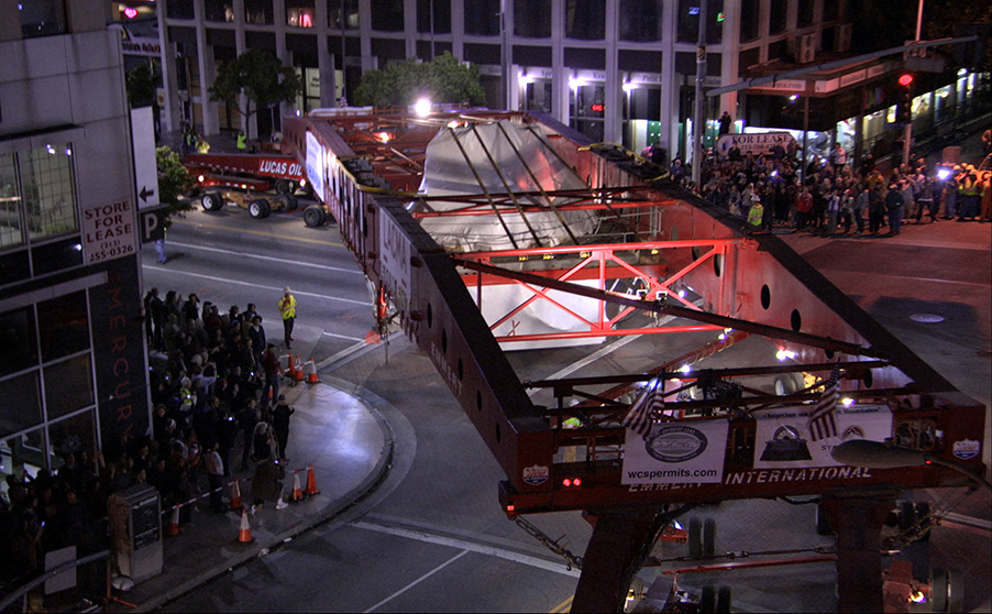 """A 340-ton granite boulder rounds Wilshire Boulevard in Los Angeles on its way to LACMA in a scene from """"Levitated Mass,"""" one of many films that tell a uniquely L.A. kind of story. Via First Run Features."""