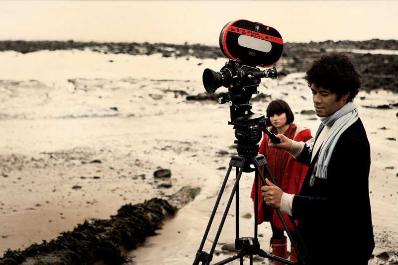 """British filmmaker Richard Ayoade with actress Yasmin Paige on the set of his 2010 feature film, """"Submarine."""" Via The Film Stage."""